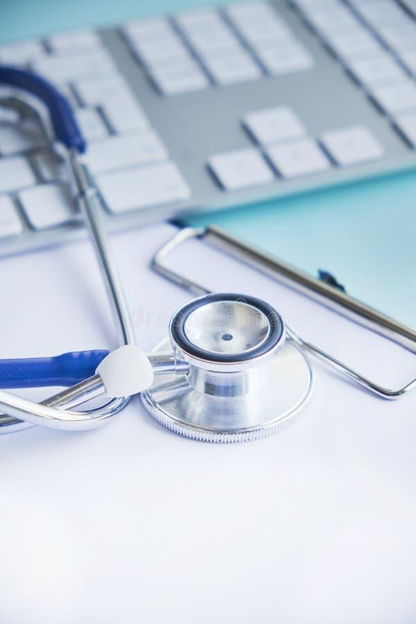Estetoscópio com prancheta e portátil na mesa, doutor que trabalha no hospital que escreve uma prescrição Cuidados médicos e médi fotografia de stock