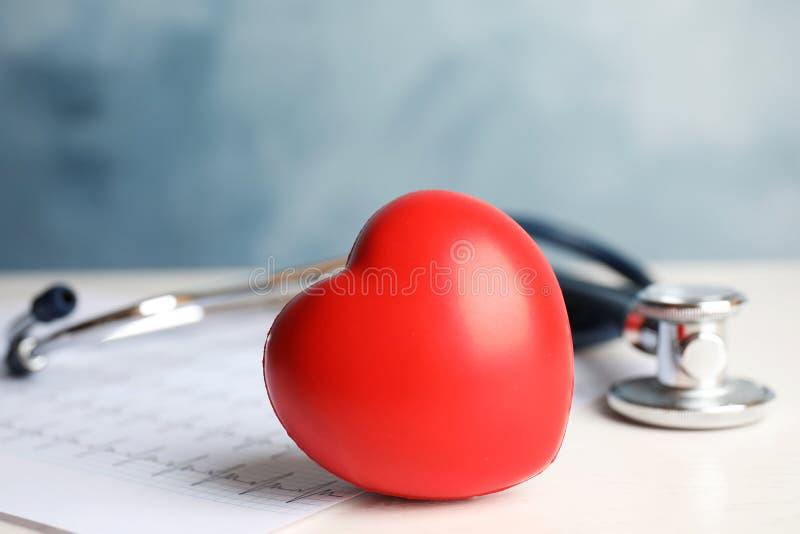 Estetoscópio, coração vermelho e cardiograma na tabela fotografia de stock royalty free