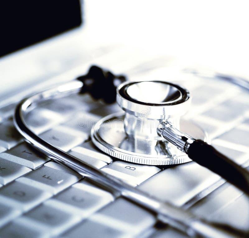 Estetoscópio de prata sobre o teclado do portátil imagens de stock