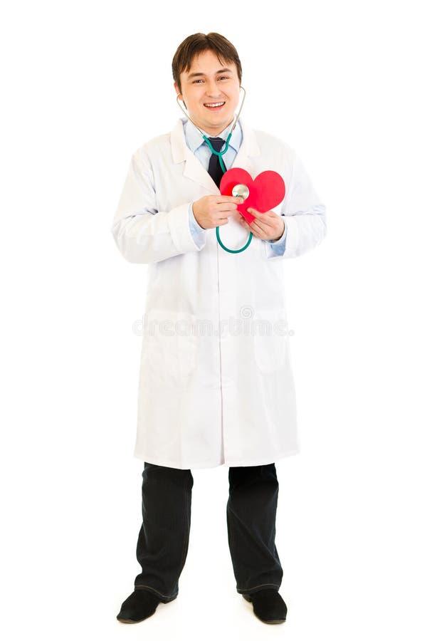 Estetoscópio de sorriso da terra arrendada do doutor no coração de papel imagem de stock