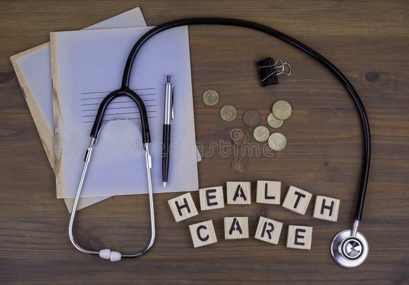 Estetoscópio, dinheiro, pena com caderno e texto: Cuidados médicos imagens de stock