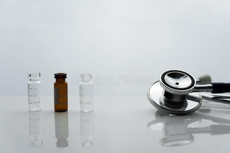 Estetoscópio do metal para o diagnóstico da saúde do doutor com farmacoterapia médico de vidro no fundo branco da clínica e do ho fotos de stock royalty free