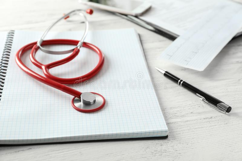 Estetoscópio e caderno médicos no fundo de madeira branco foto de stock royalty free