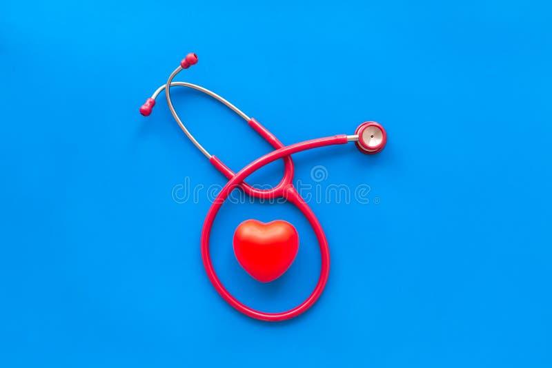 Estetoscópio e coração para o diagnóstico e a cura da doença cardíaca na opinião superior do fundo azul fotos de stock