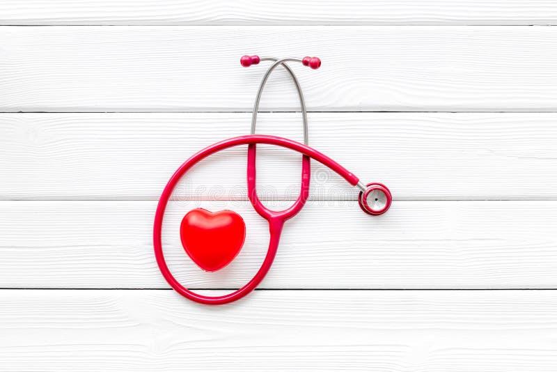 Estetoscópio e coração para o diagnóstico e a cura da doença cardíaca no modelo branco da opinião superior do fundo da mesa imagens de stock