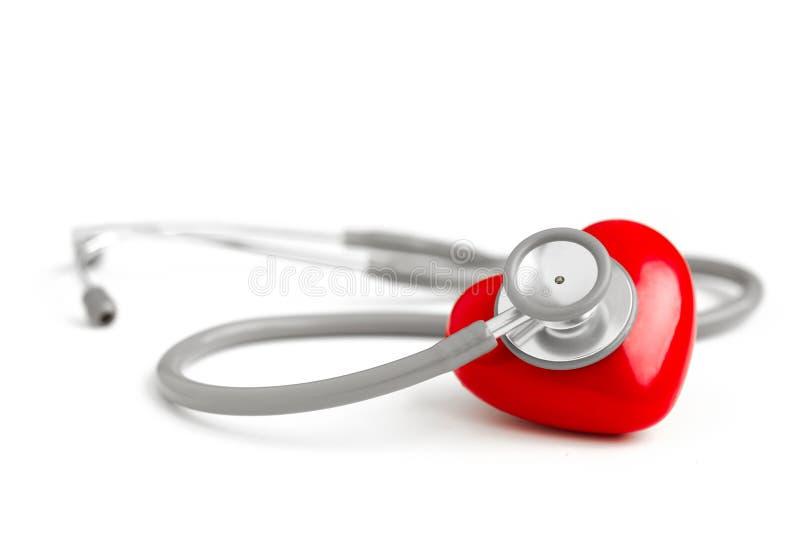 Estetoscópio e coração vermelho isolados no fundo branco imagens de stock