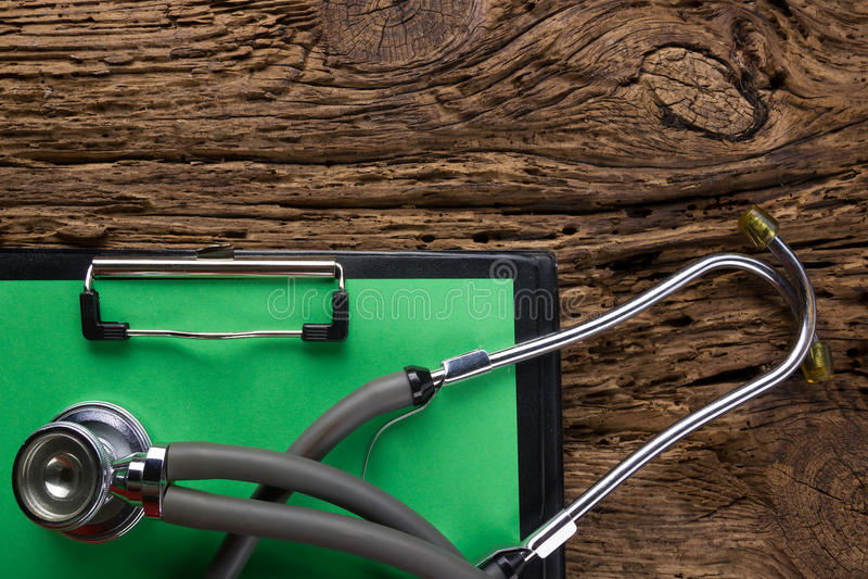 Estetoscópio e prancheta na opinião de tampo da mesa de madeira Fundo médico Conceito para a dieta, os cuidados médicos, a nutriç foto de stock