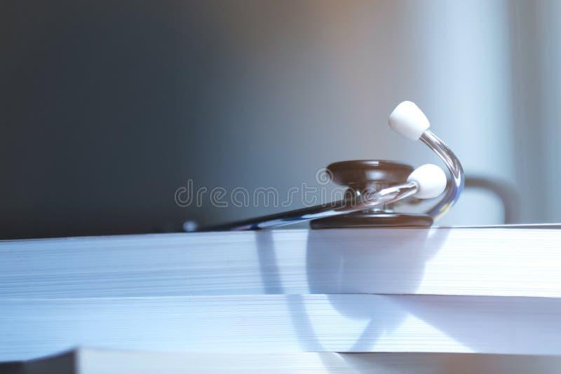 Estetoscópio em livros de texto médicos na biblioteca imagens de stock
