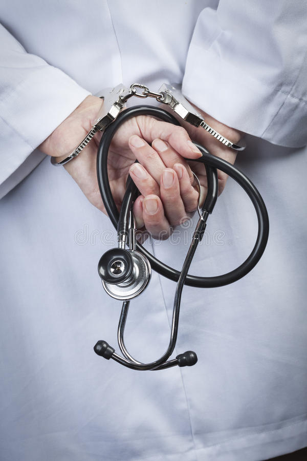 Estetoscópio fêmea de In Handcuffs Holding do doutor ou da enfermeira imagens de stock royalty free