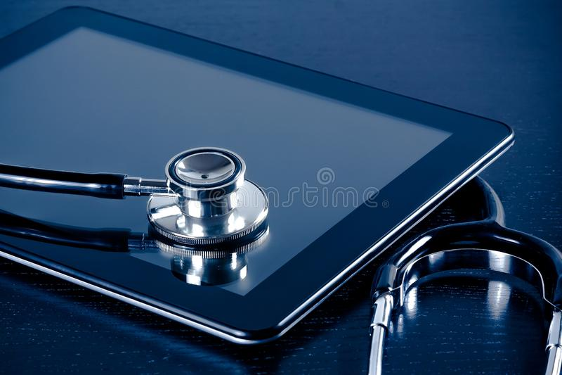 Estetoscópio médico no PC digital moderno da tabuleta no laboratório na tabela de madeira fotografia de stock
