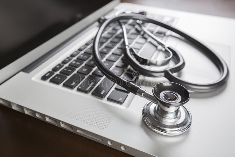 Estetoscópio médico que descansa no laptop imagens de stock