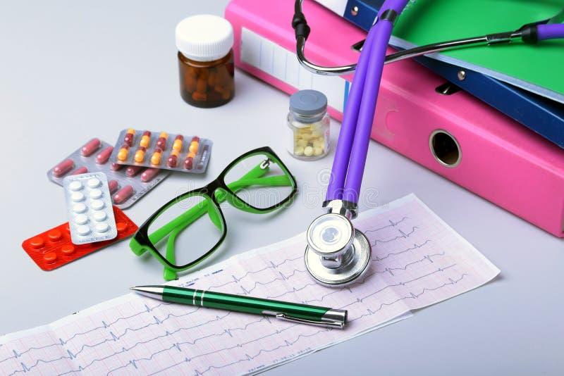 Estetoscópio médico que encontra-se na carta do cardiograma com a pilha do close up dos comprimidos Cuidado da cardiologia, saúde imagens de stock royalty free