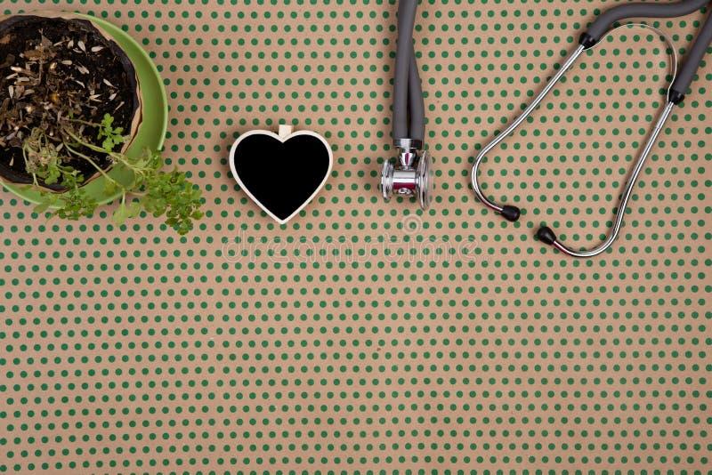 estetoscópio, quadro-negro vazio sob a forma do coração, flor em c imagens de stock royalty free