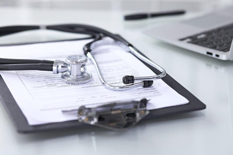 Estetoscópio que encontra-se na mesa com registros e laptop de história médica Conceito da tabela de funcionamento do ` s do dout imagens de stock