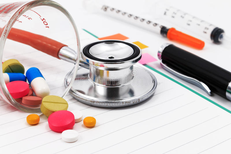 Estetoscópio vermelho, seringas, pena, e muitos comprimidos coloridos no bloco de notas vazio fotos de stock