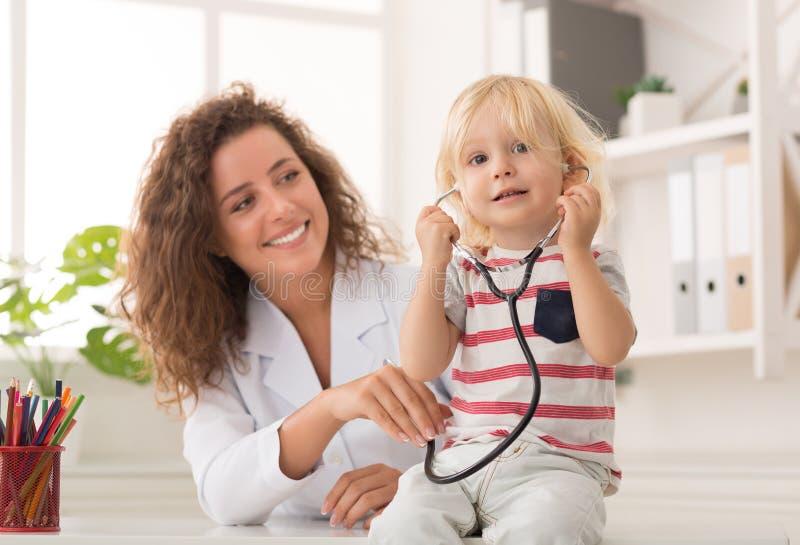 Estetoscópio vestindo do rapaz pequeno no escritório do ` s do doutor imagem de stock