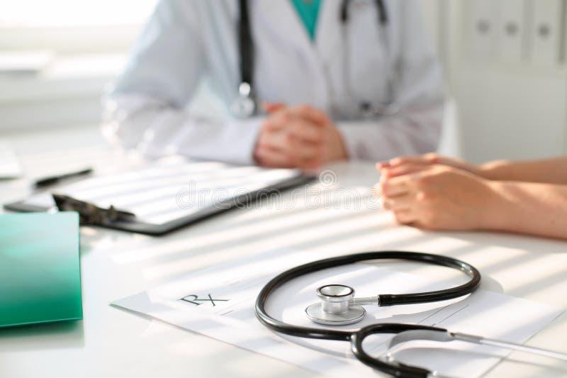 Estetoscopio al lado de la mano del doctor que tranquiliza a su paciente femenino Los éticas médicos y concepto de la confianza fotografía de archivo libre de regalías