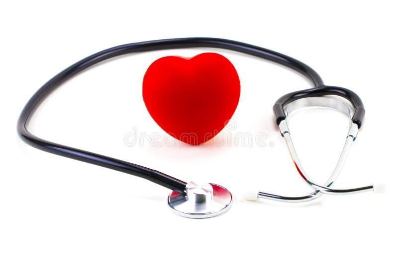 Estetoscopio alrededor de un corazón de goma rojo en un fondo blanco; estafa imagen de archivo