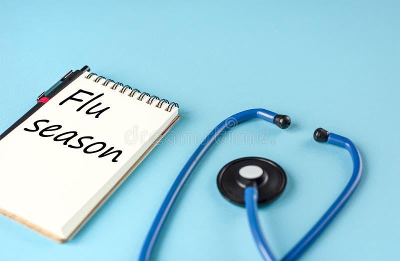 Estetoscopio azul y un cuaderno con la inscripción 'temporada de gripe 'en fondo azul foto de archivo libre de regalías