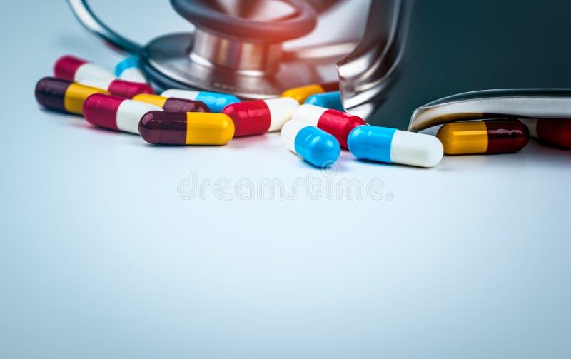 Estetoscopio con la pila de píldoras antibióticos coloridas de la cápsula en la tabla blanca con la bandeja de la droga Resistenc fotos de archivo