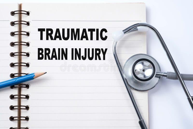 Estetoscopio en el cuaderno y el lápiz con Brain Injury traumático fotografía de archivo libre de regalías