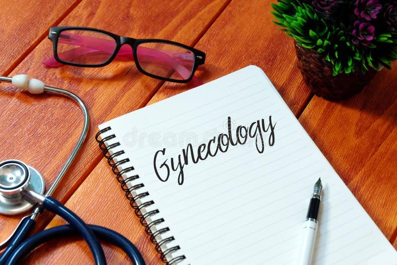 Estetoscopio, lentes, planta, pluma y cuaderno escritos con ginecología en fondo de madera Concepto de la salud foto de archivo