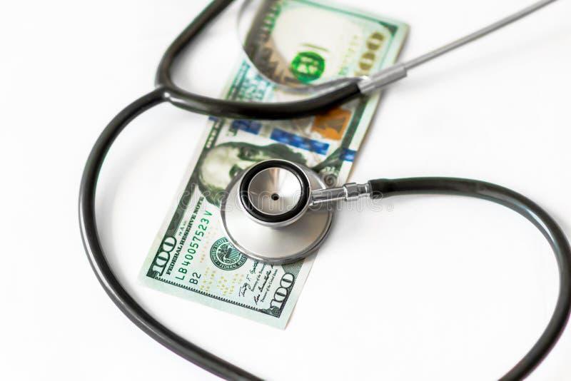 Estetoscopio médico en cientos dineros del billete de banco del dólar en el fondo blanco Concepto de costes de la atención sanita imagen de archivo
