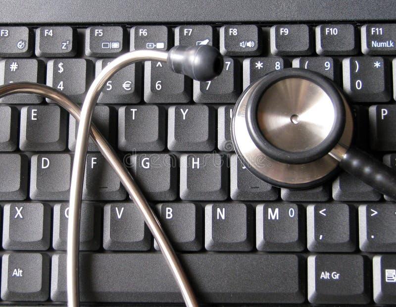 Estetoscopio médico encima del teclado de ordenador portátil Ilustrativo de la atención sanitaria y de la tecnología, informática foto de archivo libre de regalías