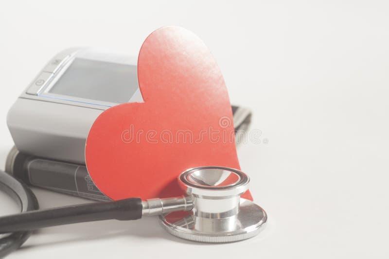 Estetoscopio, monitor digital de la presión arterial y corazón rojo foto de archivo libre de regalías