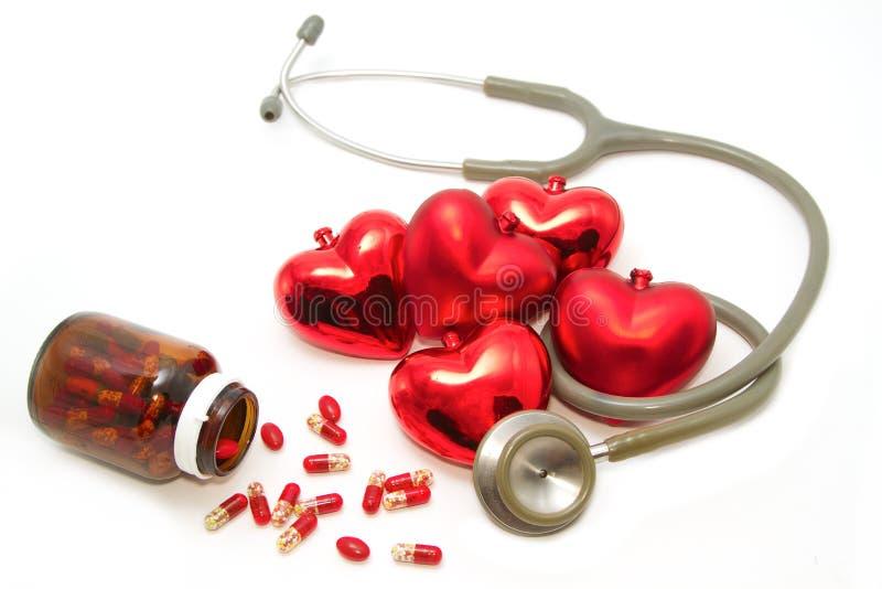 Estetoscopio que escucha el corazón y las píldoras rojos imágenes de archivo libres de regalías