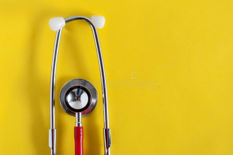 Estetoscopio rojo en un fondo amarillo Aparato m?dico Tratamiento, atenci?n sanitaria Examen del coraz?n Estudiar el pulso imagen de archivo