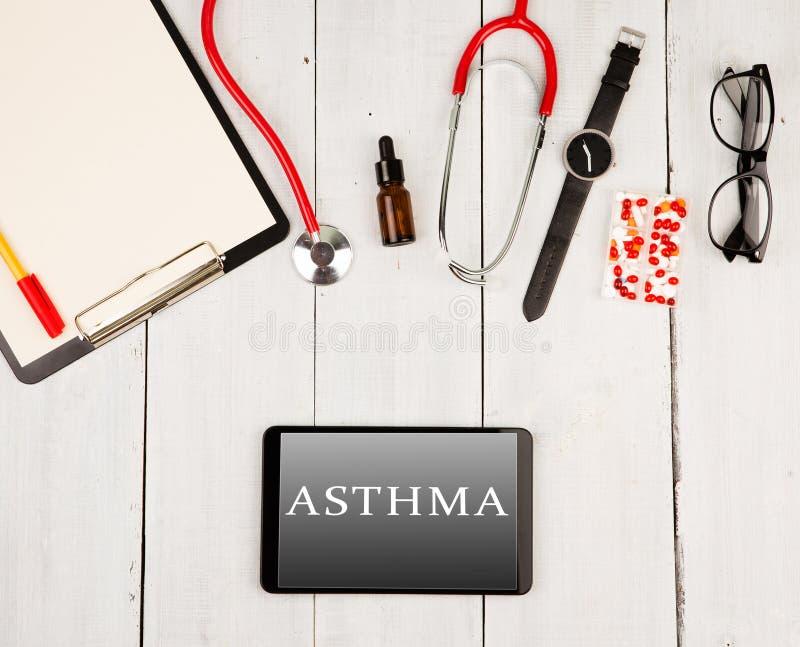 Estetoscopio, tablero, smartphone con el texto y x22; ASTHMA& x22; , vidrios, reloj y píldoras imagen de archivo
