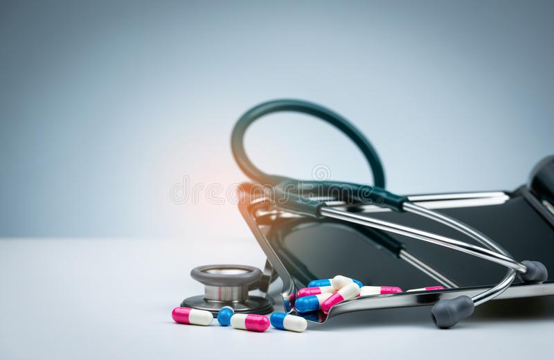 Estetoscopio verde con la pila de píldoras antibióticos de la cápsula en la bandeja de la droga y de extensión en la tabla blanca imagen de archivo libre de regalías