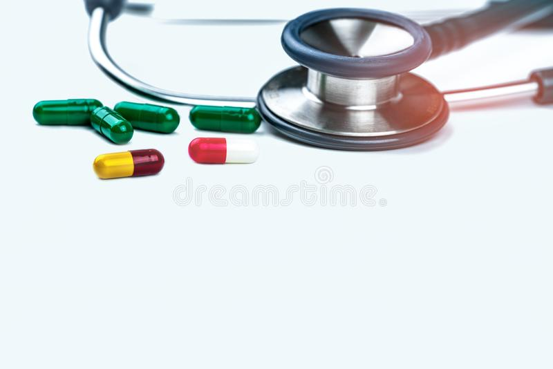 Estetoscopio verde con la pila de píldoras antibióticos de la cápsula en el fondo blanco Resistencia a los medicamentos y abuso a fotos de archivo
