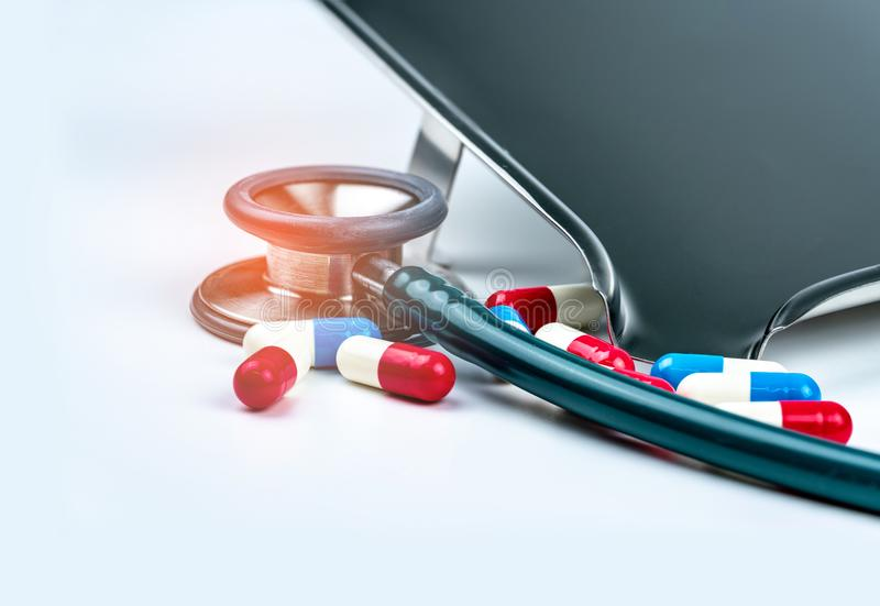 Estetoscopio verde con la pila de píldoras antibióticos de la cápsula en la tabla blanca cerca de la bandeja de la droga Resisten fotos de archivo