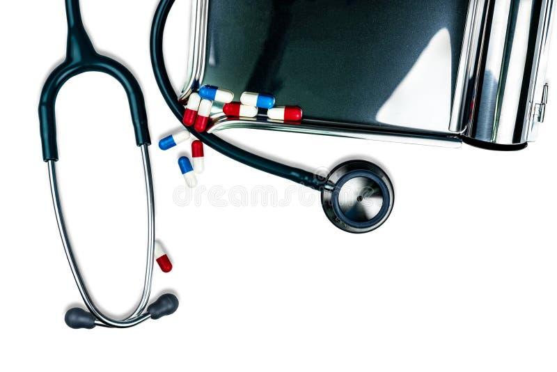 Estetoscopio verde con la pila de píldoras antibióticos de la cápsula en la tabla blanca cerca de la bandeja de la droga Resisten imágenes de archivo libres de regalías