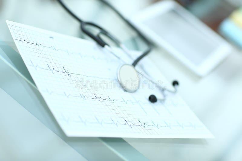 Estetoscopio y cardiograma en una tabla médica imagenes de archivo
