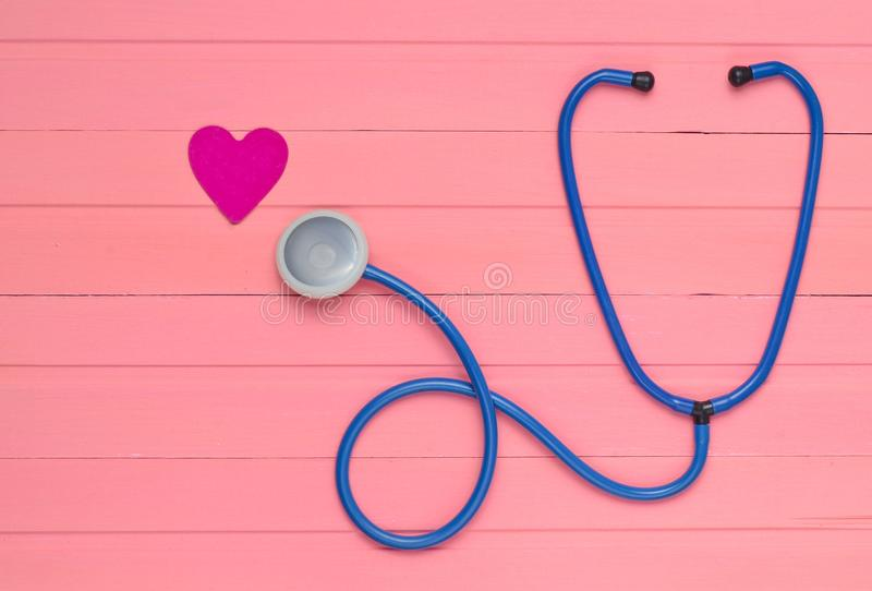 Estetoscopio y corazón en la tabla de madera del rosa en colores pastel Equipo de la cardiología para diagnosticar enfermedades c fotografía de archivo libre de regalías
