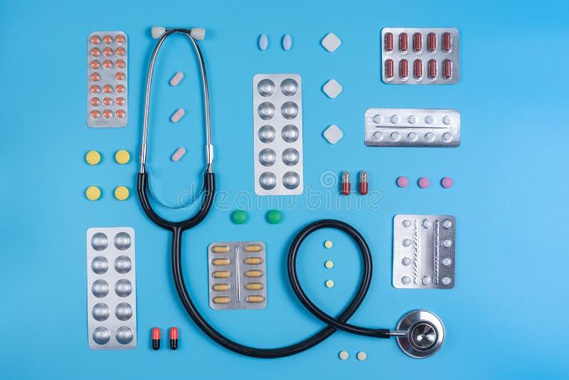 Estetoscopio y píldoras en ampollas en un fondo azul imagen de archivo