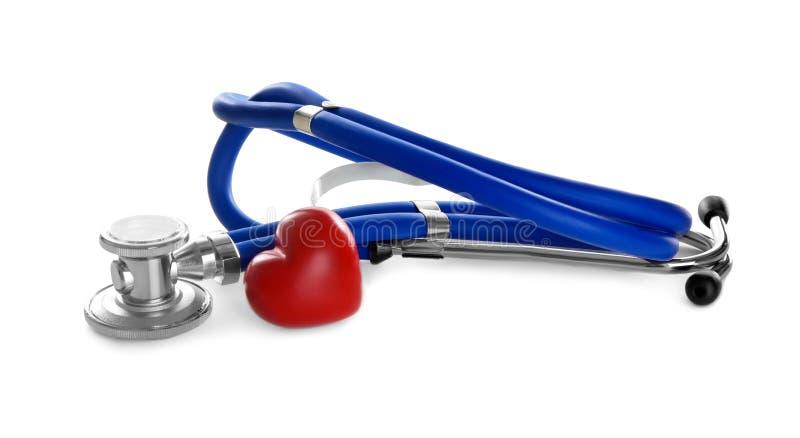 Estetoscopio y pequeño corazón rojo fotografía de archivo