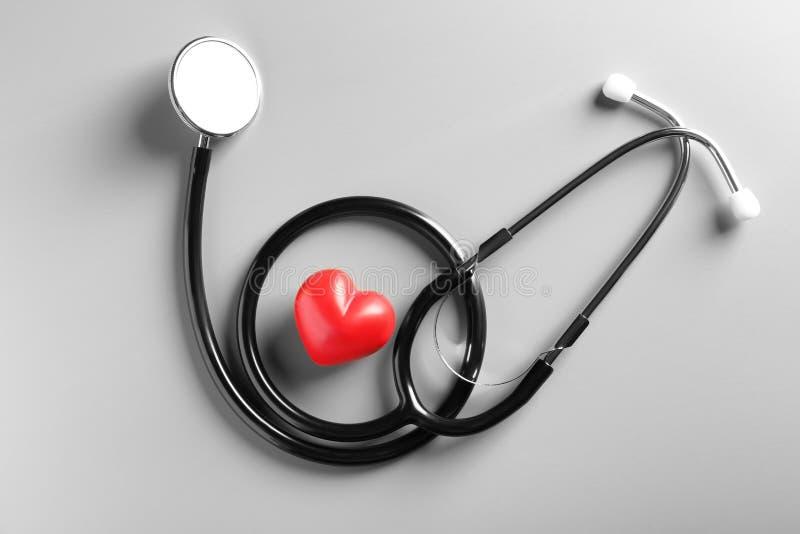 Estetoscopio y pequeño corazón rojo en fondo gris fotos de archivo