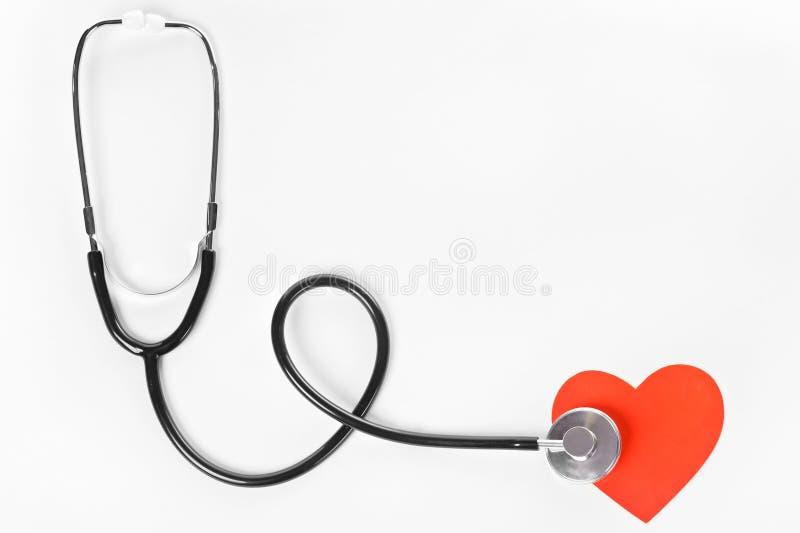 Estetoscopio y un corazón rojo fotos de archivo