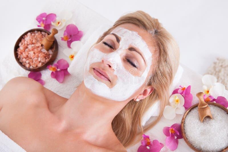 Esthéticien appliquant le masque facial sur le visage de la femme images stock