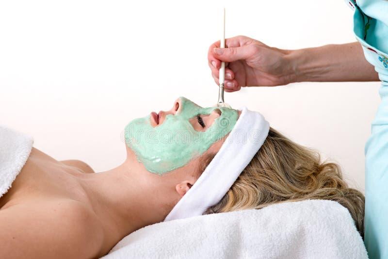 Esthéticien appliquant le masque facial vert sur une femme. images stock