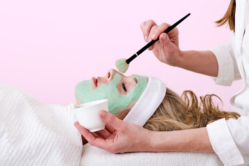 Esthéticien balayant le masque facial vert sur une femme. photographie stock libre de droits