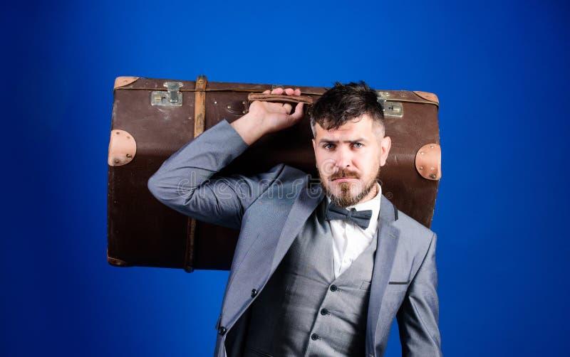 esthete elegante con el bolso del vintage Bolso pesado viajero maduro Viaje de negocios con la maleta retra Hombre barbudo en for foto de archivo