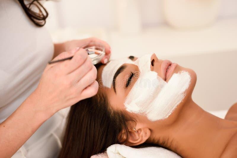 Esthetica die een masker toepassen op het gezicht van een mooie vrouw stock foto