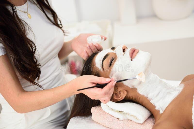 Esthetica die een masker toepassen op het gezicht van een mooie vrouw stock afbeelding