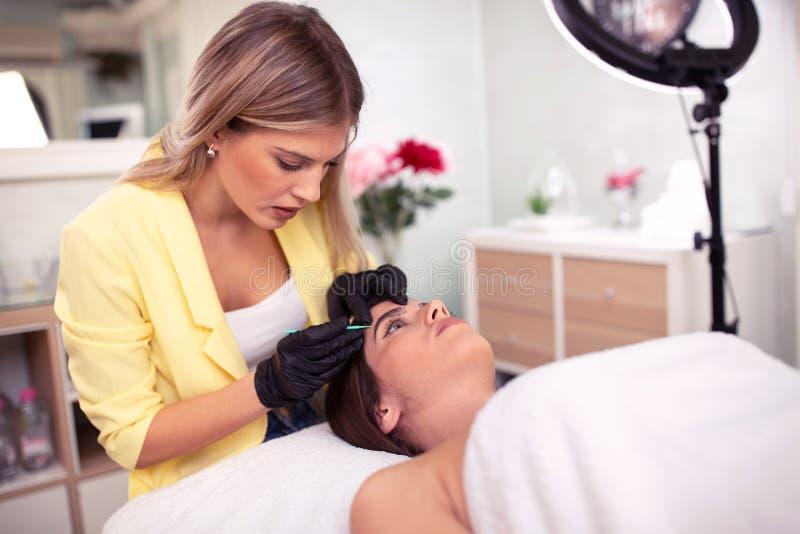 Esthetician certificado e especialista cosmético da tatuagem imagem de stock royalty free