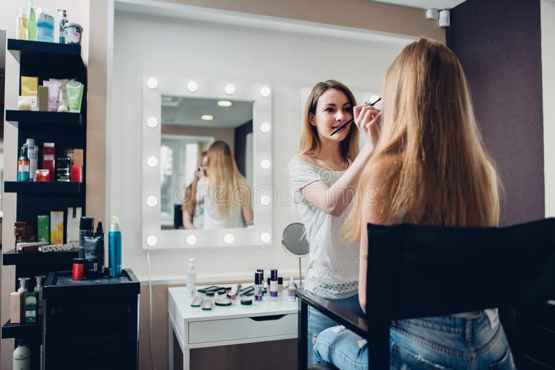 Esthetician de sexo femenino sonriente que aplica maquillaje usando cepillo al modelo femenino en estudio elegante de la belleza foto de archivo
